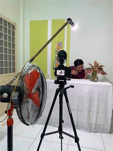 Ведущий Чыонг Джанг из шоу Nhanh Như Chớp настраивает оборудование для подготовки к съемкам дома.